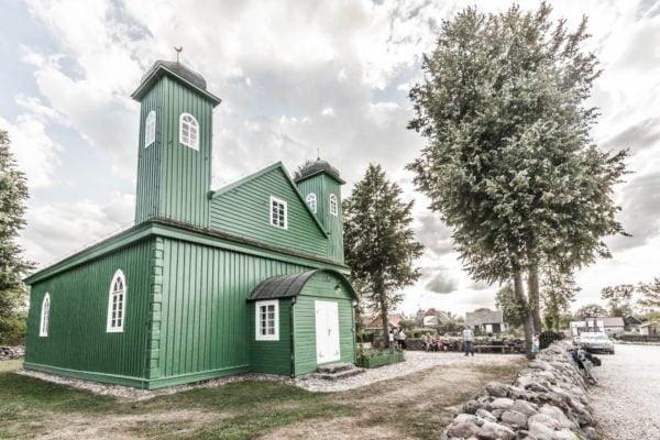 Na zdjęciu zielony, dwuwieżowy, drewniany meczet otoczony niewielkim kamiennym nasypem i kilkoma drzewami