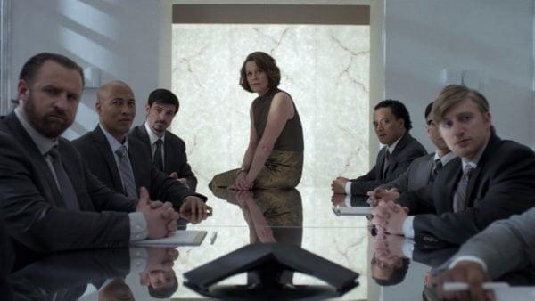 Kadr z serialu: postać grana przez Sigourney Weaver siedzi na stole na wprost kamery. Za stołem, po jego bokach, siedzi sześciu mężczyn w garniturach. Wszyscy patrzą w stronę kamery