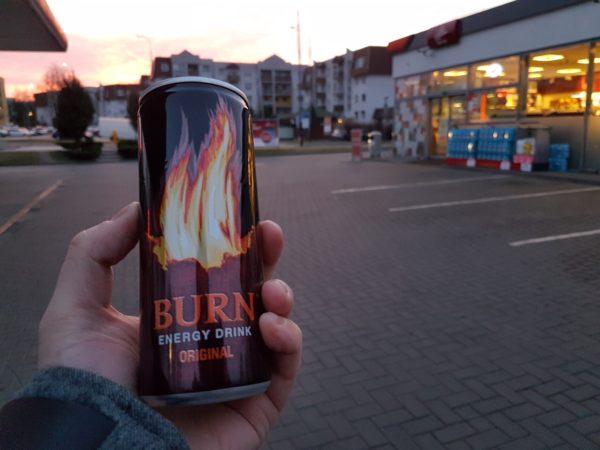 Na pierwszym planie dłoń trzymająca puszkę napoju energetycznego, w tle stacja benzynowa i wschód słońca