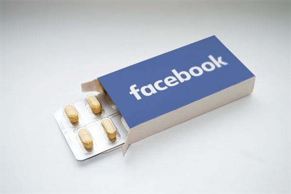 Otwarte prostokątne pudełko z wysuniętym blistrem tabletek. Na opakowaniu logo Facebooka