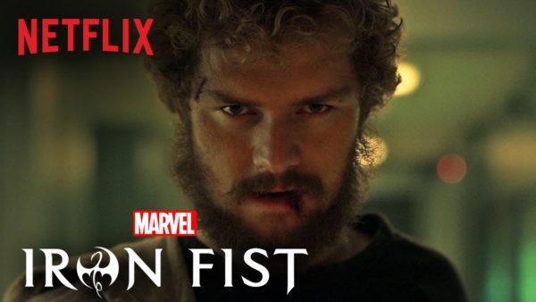 """Bliskie ujęcie twarzy Danny'ego Randa z dawno niegoloną brodą. W lewym górnym rogu logo Netfliksa, w lewym dolnym logo logo Marvela, a pod nim serialu """"Iron Fist"""""""