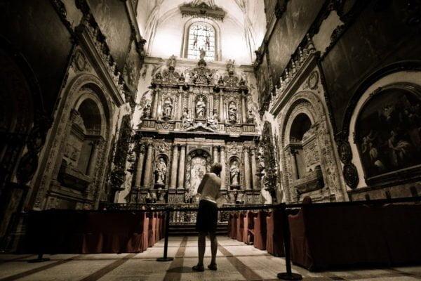 W centrum kadru widoczny barokowy ołtarz katedry w Sewilli, sfotografowany aparatem usytuowanym blisko posadzki. Nieco bliżej obserwatora, również w centrum kadru, postać spoglądającego w górę. Jasno oświetlony środek fotografii kontrastuje ze stopniowo coraz ciemniejszymi bokami