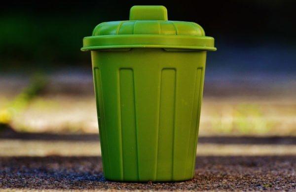 Zielony, plastikowy kosz na śmieci na rozmytym tle