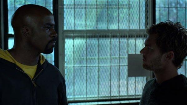 Kadr z serialu: Luke Cage i Danny Rand stoją naprzeciw siebie ukazani od piersi w górę. Spojrzenie pierwszego z nich znamionuje złość i zdecydowanie.