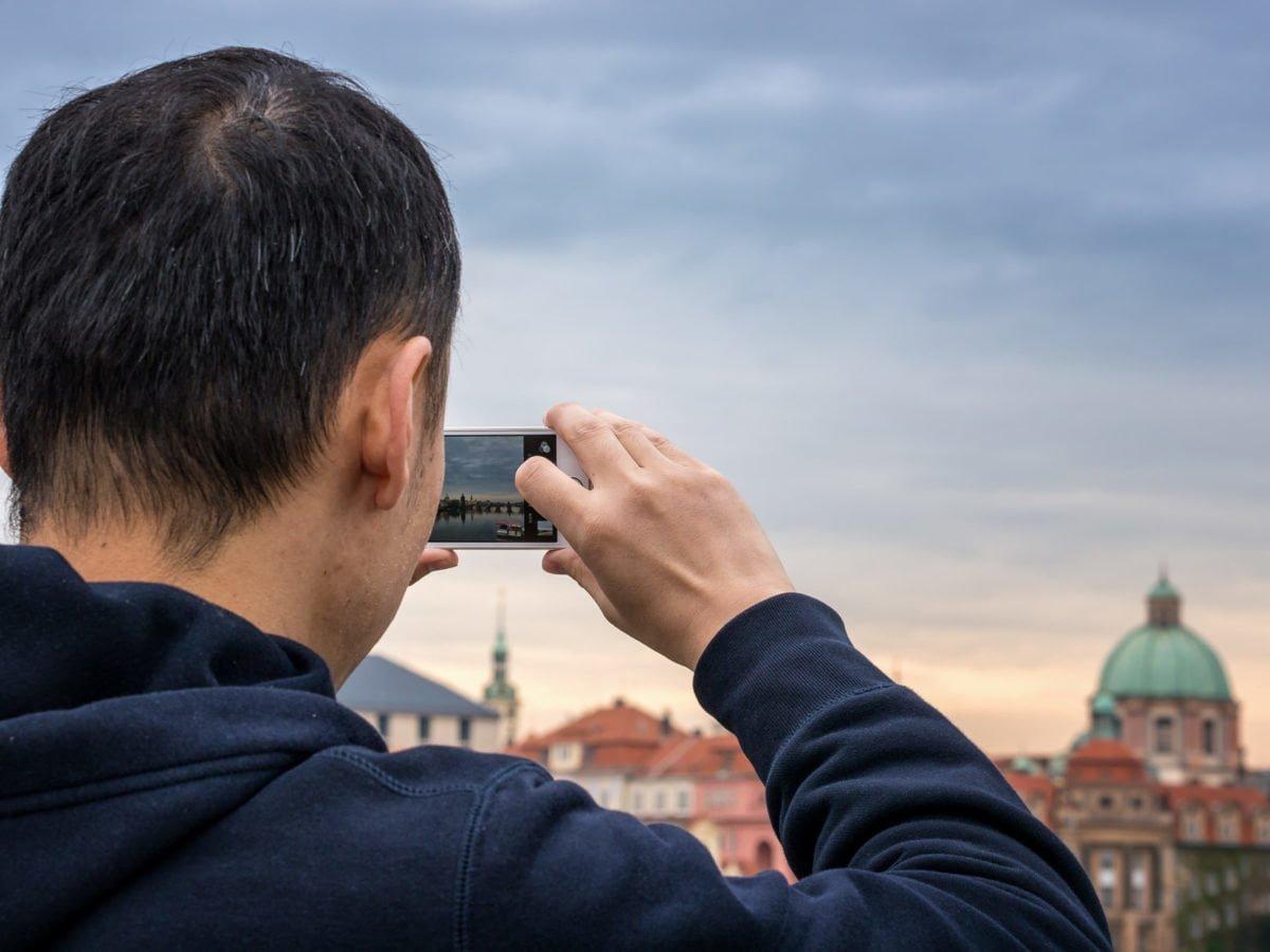 Mężczyzna widziany od tyłu, od ramion w górę, wykonuje zdjęcie smartfonem. W tle widok na stare miasto w Pradze, z widoczną kopułą kościoła św. Franciszka z Asyżu