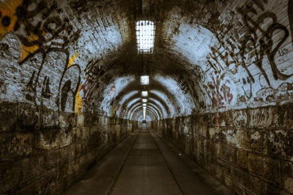 Długi tunel pokryty graffiti. Na końcu nie widać wyjścia