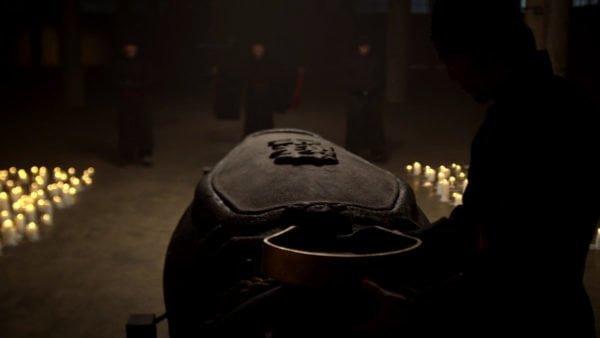 """Kadr z serialu: kamienny sarkofag w otoczeniu świec i członków """"Ręki"""""""