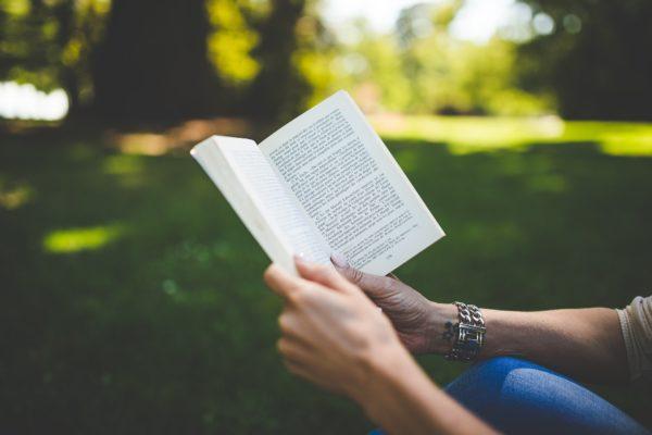 Bliżej nieznana osoba, siedząca prawdopodobnie w parku (na nieostrym tle widoczny trawnik i drzewa) trzyma w rękach książkę. Widzimy jedynie jej ręce i kolano, na którym oparta jest jedna z rąk.