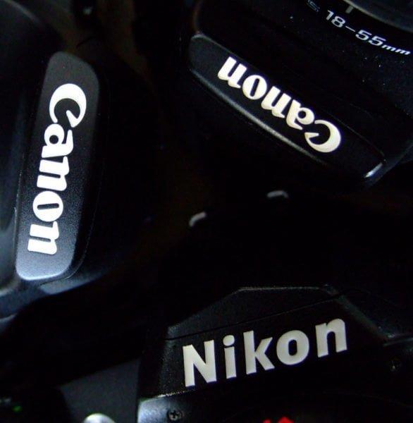Ułożone w trójkąt górne części obudów trzech lustrzanek cyfrowych z widocznymi nazwami marek (Canon, Canon i Nikon)
