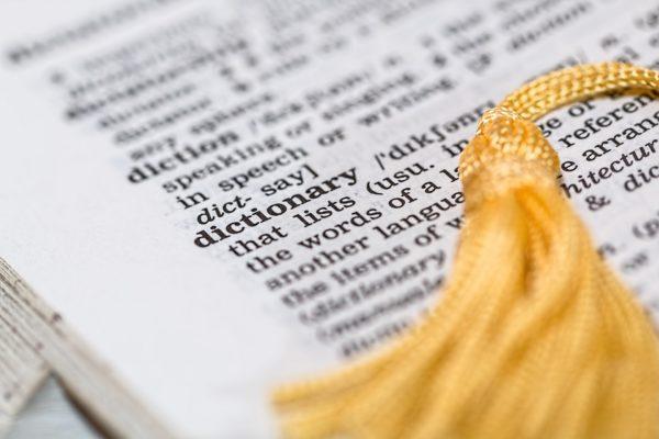"""Karta z anglojęzycznego słownika sfotografowana pod kątem ok. 45 stopni, przy niewielkiej głębi ostrości, z widocznym hasłem """"dictionary"""" (""""słownik""""). Na karcie złotego koloru frędzel na końcu sznurka służącego prawdopodobnie za zakładkę."""