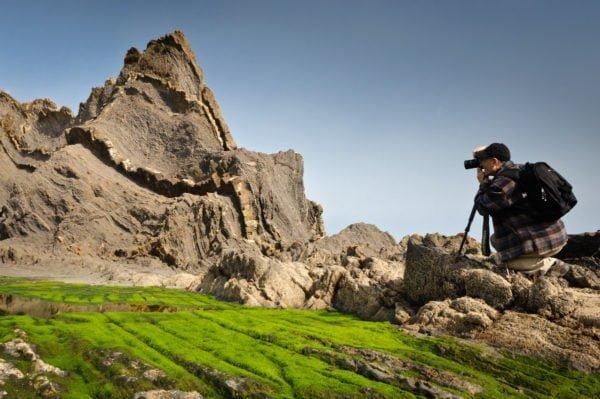 W lewej części widoczny na dalszym planie poszarpany, ostry szczyt góry czy wzniesienia na tle błękitnego nieba. Na pierwszym planie skalne podłoże pokryte mchem oraz mężczyzna w pozycji kucającej, trzymający przy oku aparat fotograficzny z obiektywem wycelowanym w stronę wspomnianego szczytu