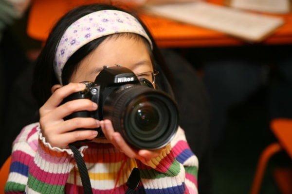 Dziewczynka ubrana w sweterek w kolorowe paski, z opaską na głowie, trzyma przy oku lustrzankę cyfrową