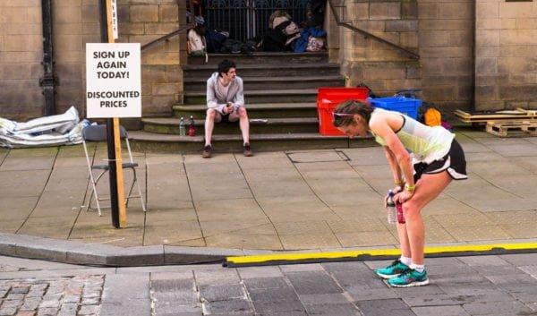 Na ulicy bliżej nieokreślonego miasta stoi kobieta w stroju biegaczki, zgięta w pół, z rękoma opartymi na kolanach, trzymająca dwa bidony