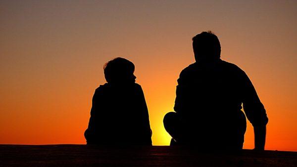 Na tle zachodzącego słońca rysują się dwie ciemne sylwetki siedzących mężczyzn: dorosłego i dziecka.
