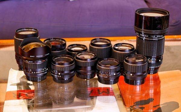 Na szklanym stole w dwóch rzędach stoi 11 analogowych obiektywów Pentaksa o różnych ogniskowych