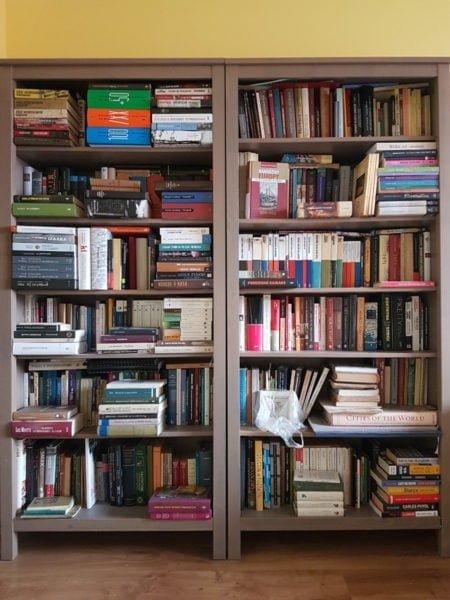 Ciasne ujęcie dwóch szarych, drewnianych regałów po sześć półek każdy, gęsto zastawionych książkami, miejscami w dwóch rzędach.