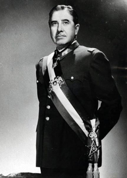 Gen. Augusto Pinochet ok. 1974 roku. Stoi wyprostowany w galowym mundurze, z rękoma za plecami, przez prawe ramię i klatkę piersiową przewieszoną ma wstęgę orderową