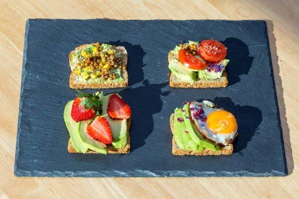 Na kamiennej, niebieskiej desce do krojenia spoczywają cztery kanapki z awokado i różnymi dodatkami, m.in. pomidorami, truskawkami i jajkiem.