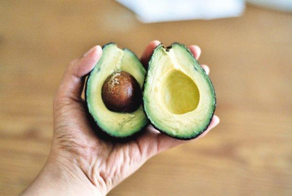 Dłoń trzymająca przekrojony na pół owoc awokado. W jednej z połówek tkwi brązowa pestka.