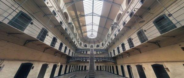 Szerokokątny widok na wnętrze więzienia. Po obu stronach długiego, szerokiego hallu widać kilka pięter rzędów drzwi do cel.