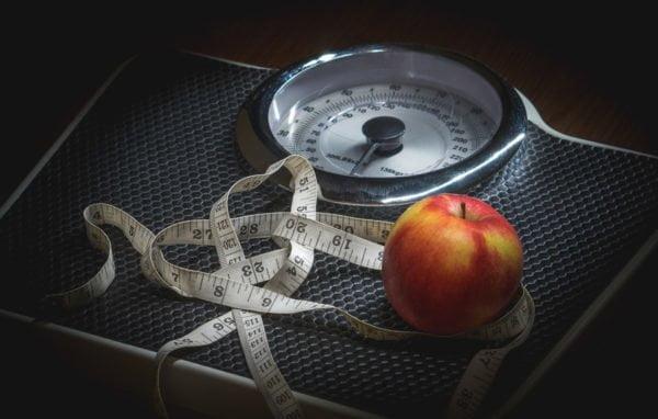 Na zdjęciu szara domowa waga łazienkowa, a na niej centymetr oraz jabłko